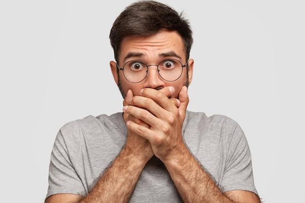 Portret van aantrekkelijke man met angstige uitdrukking, bedekt de mond met beide handpalmen, is stomverbaasd, merkt iets vreselijks op, gekleed in grijze kleding, geïsoleerd over witte muur