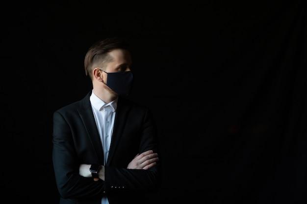 Portret van aantrekkelijke man met zwart pak en beschermend masker voor preventie covid-19 geïsoleerd