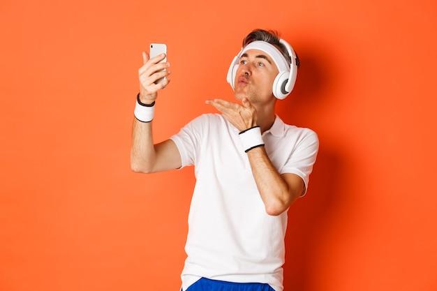 Portret van aantrekkelijke man van middelbare leeftijd in uniform gym, hoofdtelefoon dragen