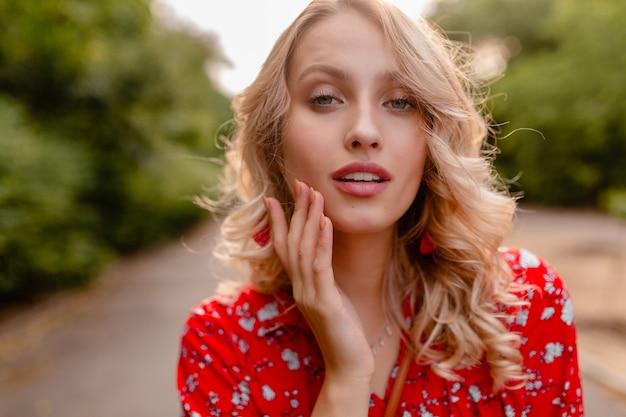 Portret van aantrekkelijke modieuze blonde glimlachende vrouw in rode de manieruitrusting die van de blousezomer oorringen het glimlachen dragen