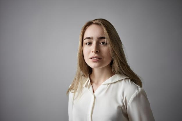 Portret van aantrekkelijke modieuze jonge blonde blanke dame met sproeten, losse kapsel en geen make-up poseren in studio dragen wit overhemd op grijze copyspace muur, camera kijken