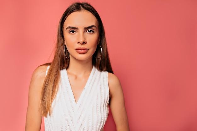 Portret van aantrekkelijke mooie vrouw met lang haar, gekleed in witte jurk poseren over roze muur close-up