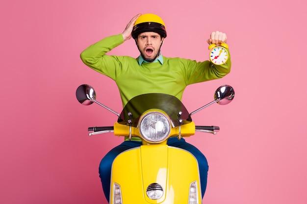Portret van aantrekkelijke ongelukkige bezorgd man rijden bromfiets bedrijf wekker