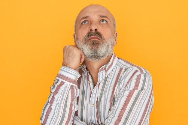 Portret van aantrekkelijke ongeschoren bejaarde man met kaal hoofd opzoeken met peinzende doordachte ogen, nadenken over probleem, op zoek naar oplossing. menselijke gevoelens, reactie en lichaamstaal