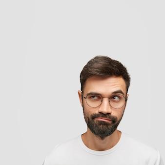 Portret van aantrekkelijke ongeschoren man kijkt met verbazing opzij, diep in gedachten