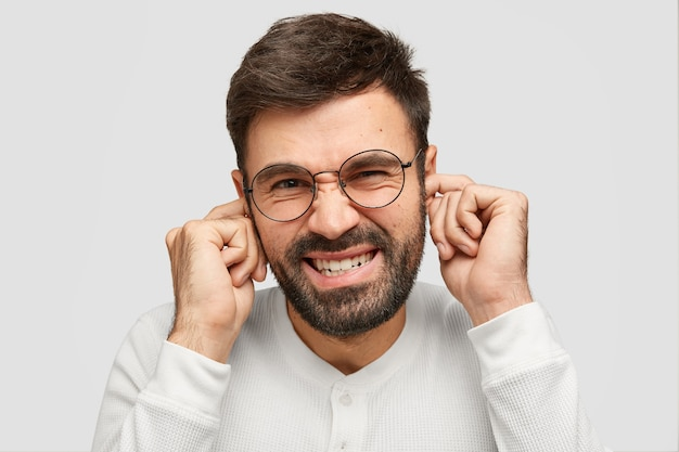 Portret van aantrekkelijke ongeschoren man pluggs oren als vervelend geluid hoort, fronst gezicht, klemt tanden