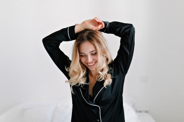 Portret van aantrekkelijke opgewonden mooi meisje in zwarte nachtkleding wakker op bed in de ochtend in modern appartement.