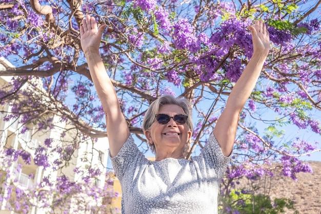 Portret van aantrekkelijke oudere vrouw met opgeheven armen onder een paarse plant in volle bloei