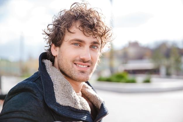 Portret van aantrekkelijke positieve glimlachende gelukkige gekrulde jonge man in zwarte jas