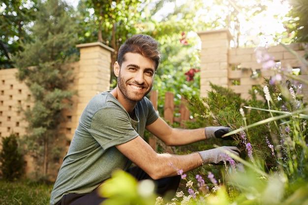 Portret van aantrekkelijke rijpe bebaarde spaanse bloemist glimlachend in de camera, waakt over bloemen in de tuin in de buurt van plattelandshuis met gelukkige en ontspannen gezichtsuitdrukking close-up