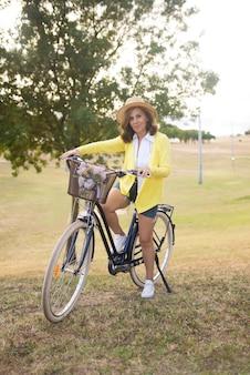 Portret van aantrekkelijke rijpe vrouw die op de fiets rijdt