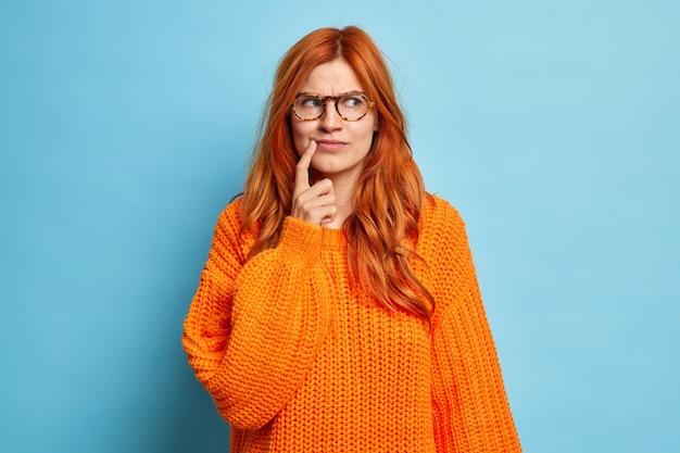 Portret van aantrekkelijke roodharige jonge vrouw houdt wijsvinger in de buurt van de hoek van de lippen iets te veel nadenkt en besluit draagt gebreide trui.