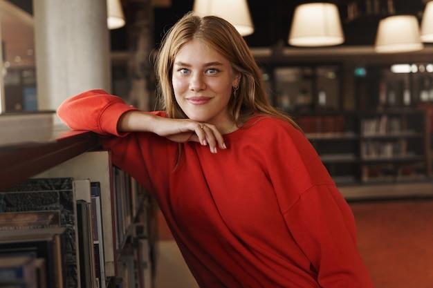 Portret van aantrekkelijke roodharige vrouwelijke student, leunend op een boekenplank in een bibliotheekzaal en glimlachende camera.