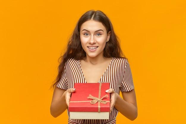 Portret van aantrekkelijke schattige jonge europese vrouw in gestreepte jurk met rode doos