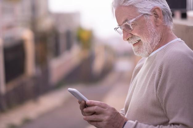 Portret van aantrekkelijke senior man die buiten staat bij zonsondergang met behulp van mobiele telefoon. aantrekkelijke oudere gepensioneerde die technologie gebruikt
