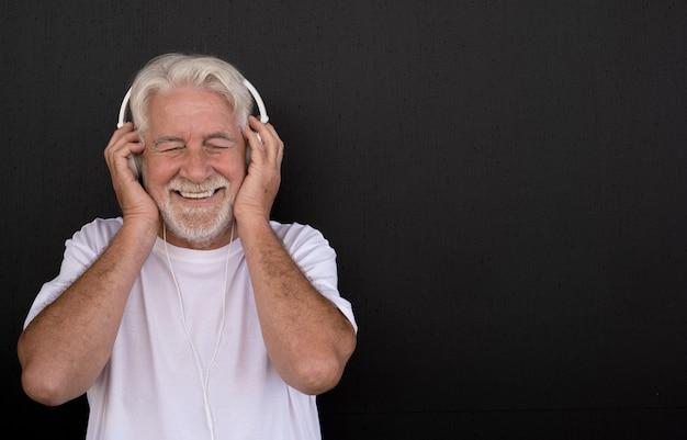 Portret van aantrekkelijke senior man luisteren naar muziek met koptelefoon zwarte achtergrond