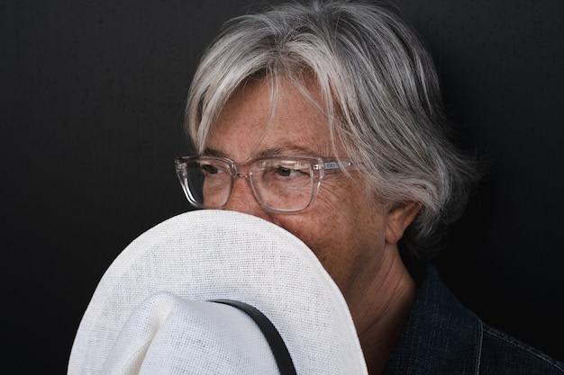 Portret van aantrekkelijke senior vrouw met bril verborgen door strohoed. zwarte achtergrond