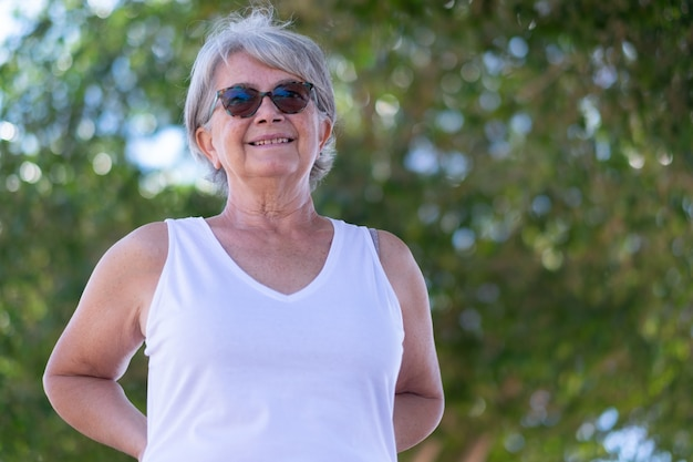 Portret van aantrekkelijke senior vrouw wit gekleed in de buitenlucht onder een boom