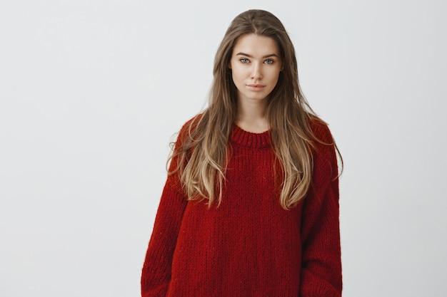 Portret van aantrekkelijke sensuele jonge 25s vrouw in rode gezellige trui zitten comfortabel thuis, genieten van sneeuw vallen straten vallen, staren poseren tegen