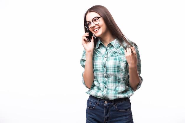 Portret van aantrekkelijke spaanse vrouw op blauw t-shirt die op haar cel spreekt terwijl status en op studio glimlacht