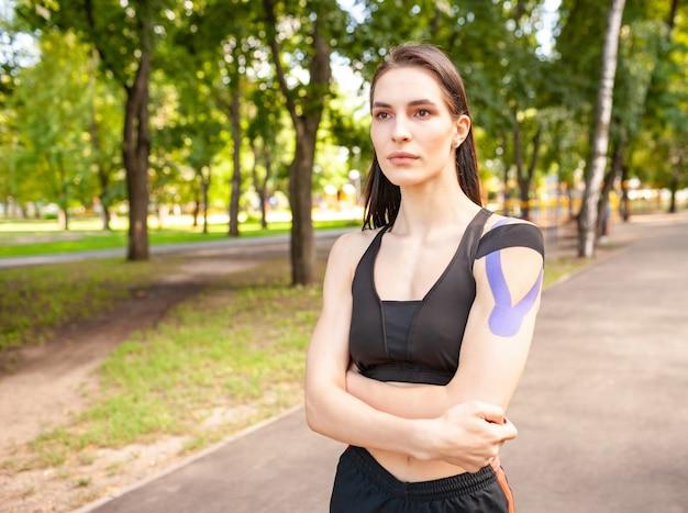 Portret van aantrekkelijke spier donkerbruine vrouw die zwarte sportenuitrusting draagt
