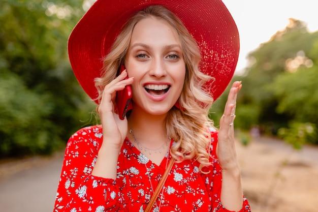 Portret van aantrekkelijke stijlvolle blonde lachende vrouw in rode strooien hoed en blouse zomer mode outfit praten over telefoon positieve gebaar emotie