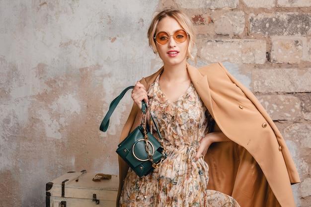 Portret van aantrekkelijke stijlvolle blonde vrouw in beige jas wandelen in straat tegen vintage muur