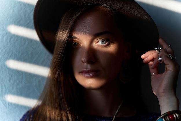 Portret van aantrekkelijke stijlvolle brunette vrouw in een hoed met ringen met overlays schaduw op de ogen