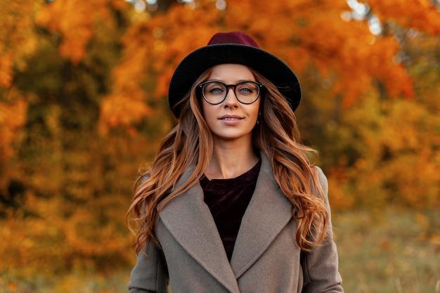 Portret van aantrekkelijke stijlvolle jonge vrouw in trendy bril in een vintage hoed in een elegante jas op een achtergrond van een bomen met gouden bladeren in het park. mooi europees hipster meisje buitenshuis.