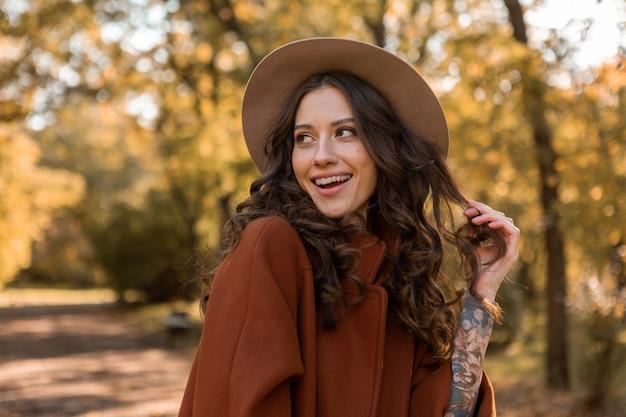 Portret van aantrekkelijke stijlvolle lachende vrouw met lang krullend haar wandelen in park gekleed in warme bruine jas herfst trendy mode, streetstyle hoed dragen