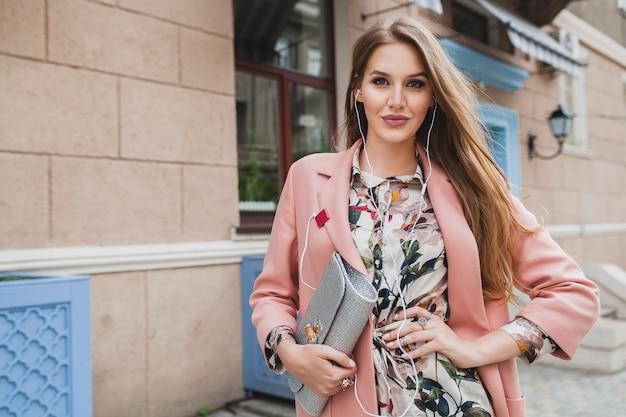 Portret van aantrekkelijke stijlvolle lachende vrouw stad straat in roze jas en bloemen jurk lopen en luisteren naar muziek