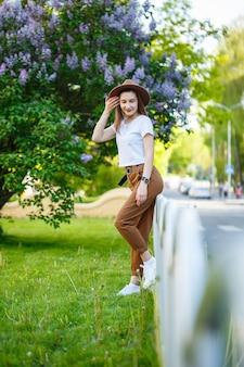 Portret van aantrekkelijke stijlvolle vrouw in een hoed met lang blond haar in het park, gekleed in een wit t-shirt en bruine broek.