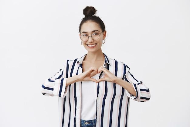 Portret van aantrekkelijke tedere vrouwelijke vrouw met broodje kapsel in stijlvolle kleding en glazen hart met handen over de borst vormgeven en breed glimlachend terwijl het uiten van liefde en sympathie
