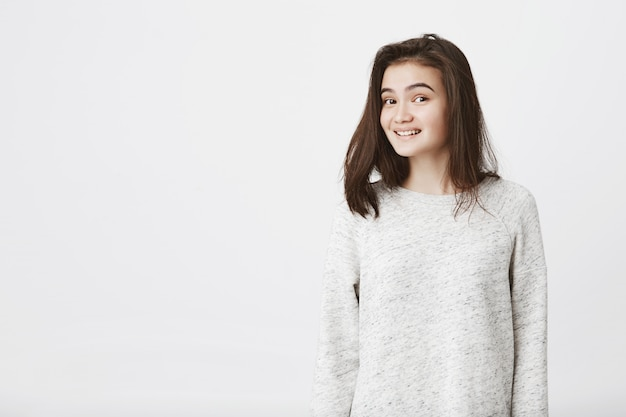 Portret van aantrekkelijke trendy vrouw met opgeheven wenkbrauwen, angstig glimlachend