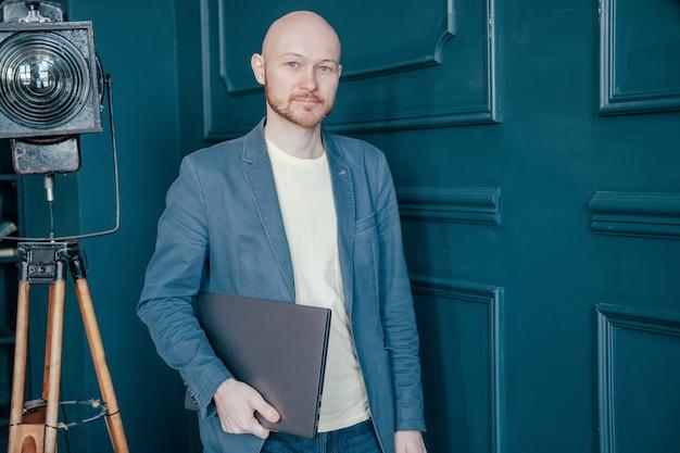 Portret van aantrekkelijke volwassen succesvolle kale bebaarde man in pak met laptop in de buurt van blauwe muur