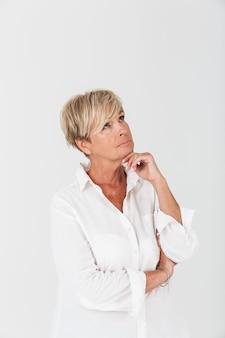 Portret van aantrekkelijke volwassen vrouw met kort blond haar die copyspace bekijkt die over witte muur in studio wordt geïsoleerd