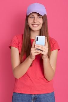 Portret van aantrekkelijke vrij vrolijke dame bedrijf in handen mobiele telefoon, spel spelen via smartphone terwijl het hebben van vrije tijd, geïsoleerd over heldere roze muur.