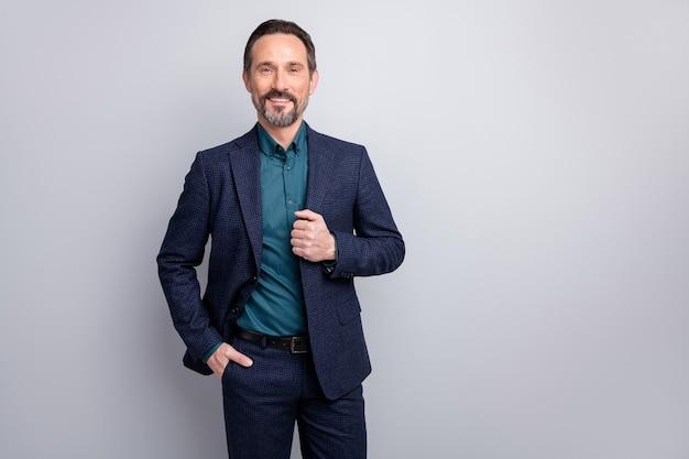 Portret van aantrekkelijke vrolijke man in pak geïsoleerde grijze kleur achtergrond
