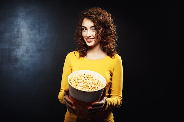 Portret van aantrekkelijke vrouw die aan popcorn met vrolijke glimlach behandelt