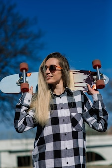 Portret van aantrekkelijke vrouw die in zonnebril status met longboard, sport en hobby glimlachen