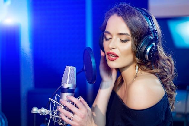 Portret van aantrekkelijke vrouw die met perfecte make-up een lied in een professionele studio opnemen.