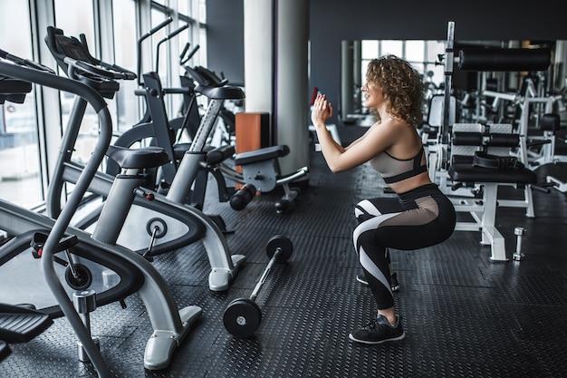 Portret van aantrekkelijke vrouw die traint in de fitnessstudio in de buurt van simulatoren