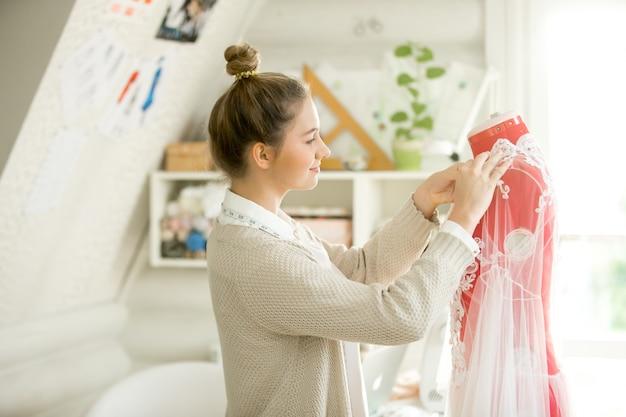 Portret van aantrekkelijke vrouw dressing een kleermaker mannequin