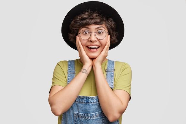 Portret van aantrekkelijke vrouw houdt de handen op de wangen en kijkt met verbazing