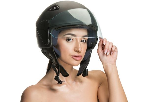 Portret van aantrekkelijke vrouw in motorhelm op witte studioachtergrond. schoonheids-, huid- en gezichtsbeschermingsconcept