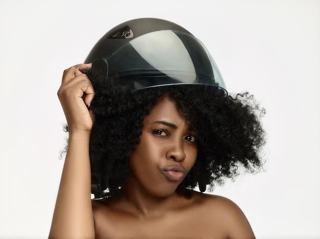 Portret van aantrekkelijke vrouw in motorhelm op witte studiomuur