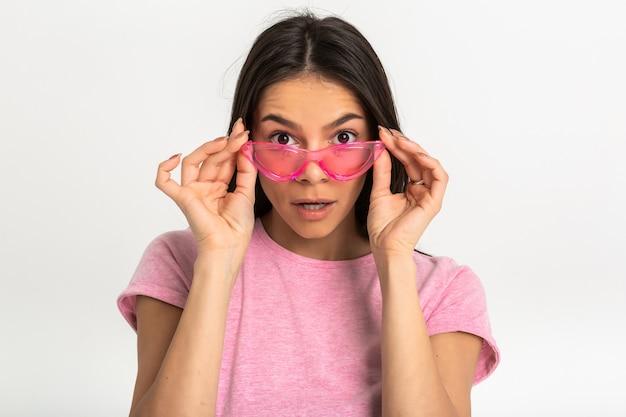 Portret van aantrekkelijke vrouw in roze t-shirt met stijlvolle zonnebril geïsoleerd verrast geschokt gezicht uitdrukking op zoek
