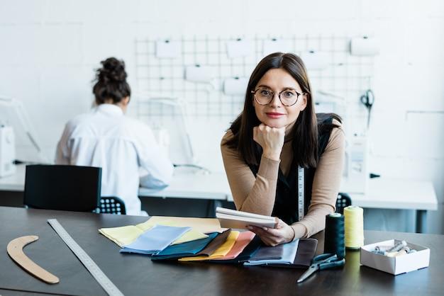 Portret van aantrekkelijke vrouw, leunend op tafel met textielpatronen in de ontwerpstudio van de kleding