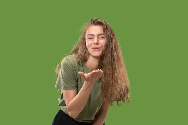 Portret van aantrekkelijke vrouw met kus op lippen. groene studio. mooi vrouwelijk portret.