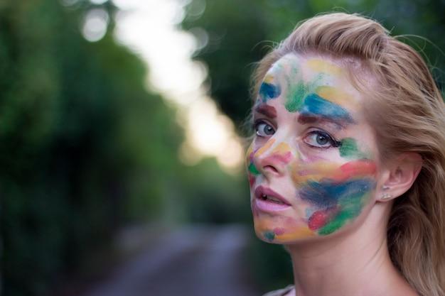 Portret van aantrekkelijke vrouw met multi gekleurd gezicht in het openbare park